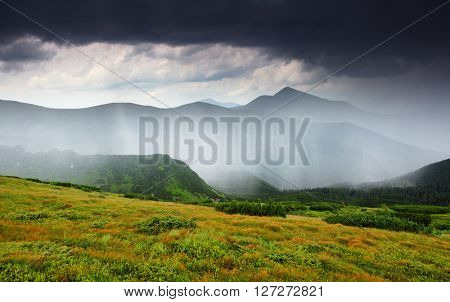 Wonderful view of the rain clouds over the wooded mountains. Dramatic and picturesque scene. Location place National park Chornogora, Carpathian, Ukraine, Europe. Artistic picture. Beauty world.
