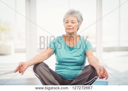 Senior woman performing yoga while sitting at home