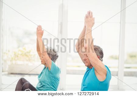 Senior couple performing yoga with arms raised at home
