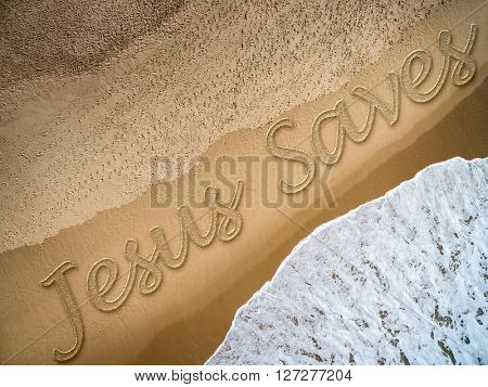 Jesus Saves written on the beach