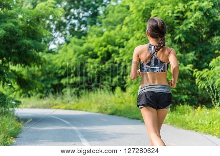 Active lifestyle girl runner running in summer city park living a healthy life. Jogger athlete woman from behind training cardio for weight loss of back thigh cellulite. Road to success to a fit body.