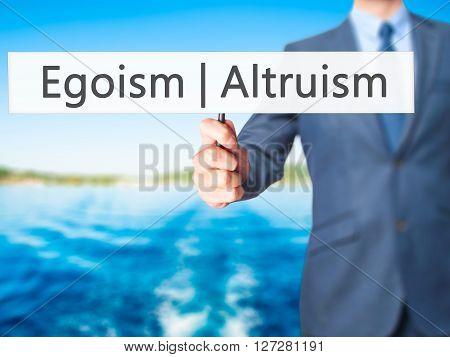 Altruism  Egoism - Businessman Hand Holding Sign
