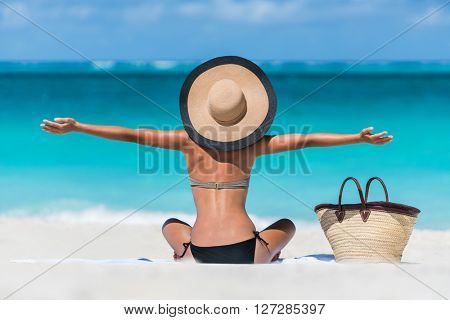 Summer vacation happy carefree joyful bikini woman arms outstretched in happiness enjoying tropical beach destination. Holiday girl sitting with sun hat relaxing from behind on Caribbean vacation.
