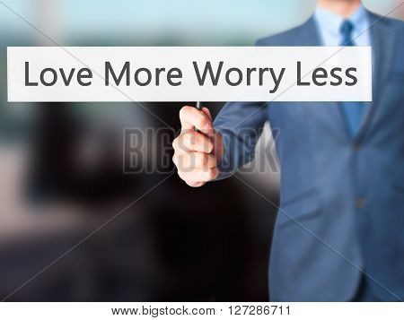 Love More Worry Less - Businessman Hand Holding Sign