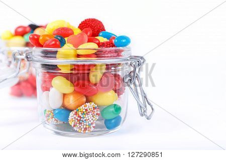 Closeup many different colorful candies and chewing gum in the glass jar on a white background with space for your text