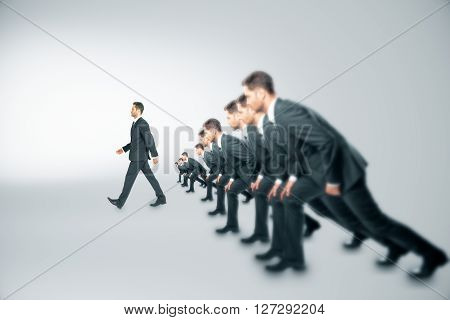 Competition concept with many businessmen about to run and one walking ahead of them on grey background