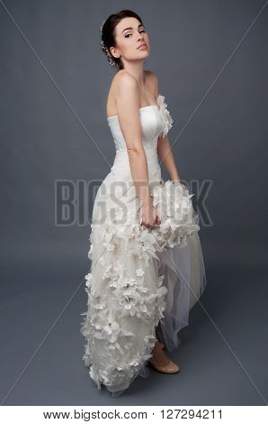Bridal fashion hairstyle and makeup. Brunette bride in wedding dress and beaded headpiece on gray backdrop. ** Note: Soft Focus at 100%, best at smaller sizes