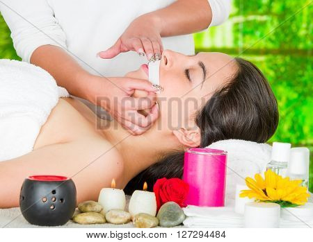 Woman headshot profile, lying with eyes closed and hand applying wax paper to upper lip of client.