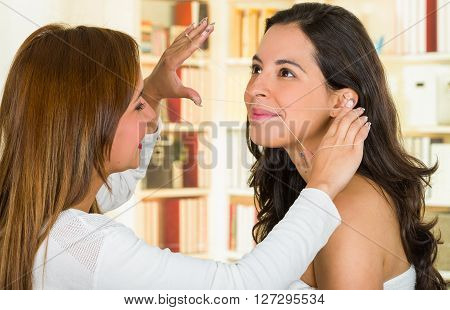 Cosmetologist performing facial hair removal using threading technique on brunette patient smiling.