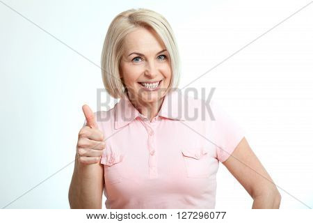 Happy attractive middle aged woman showing thumbs up, okay. Isolated square