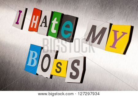 Hate My Boss written with color magazine letter clippings on metal background. Design for business relationship and work. Selective focus.