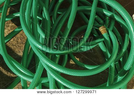 A tangled up mess of a used plastic water hose pipe on a concrete patio surface on a sunny morning.