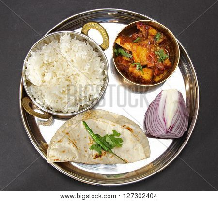Overhead view of an Indian vegetarian meal comprising of yellow lentil daal or soup with Karahi paneer rice and chapati on a thali or plate on a moody background.