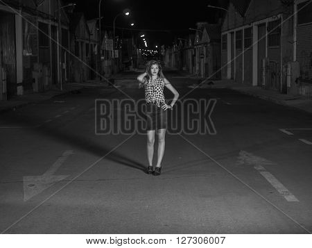 pretty blonde standing on the road at night with one hand on the head