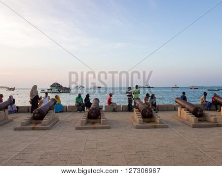 STONE TOWN ZANZIBAR - MARCH 28 2016: Cannons in the Waterfront of Stone Town Zanzibar. Local people and tourist enjoy a worm evening in the Waterfront.