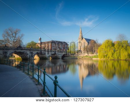 View along the river Severn to the English Bridge, Shrewsbury and a church and prominent willow tree, England, UK.