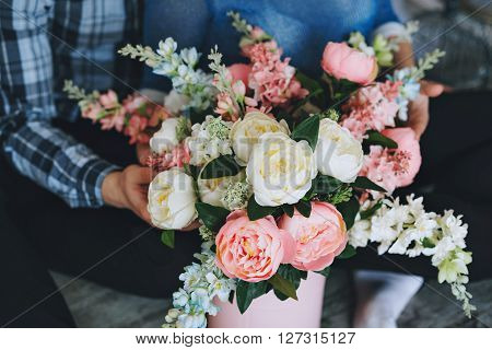 A bouquet of flowers in a pink vase.With colors of rose quartz and sky blue