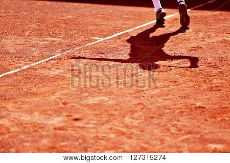 Shadow of a tennis player in action on a clay court
