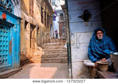 VARANASI, INDIA - JANUARY 4, 2013: Elderly man in a cape sitting alone on the street of the ancient indian city on January 4, 2013. The 2525 km Ganges river rises in Indian Uttarakhand flows into Bangladesh