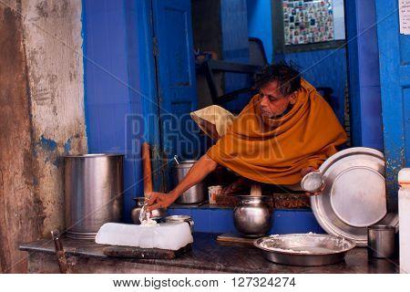 VARANASI, INDIA - JANUARY 2, 2013: Indian milkman prepares the popular drink Lassi by an ancient recipe sitting on a doorstep on January 2, 2013. Varanasi urban agglomeration had a population of 1435113