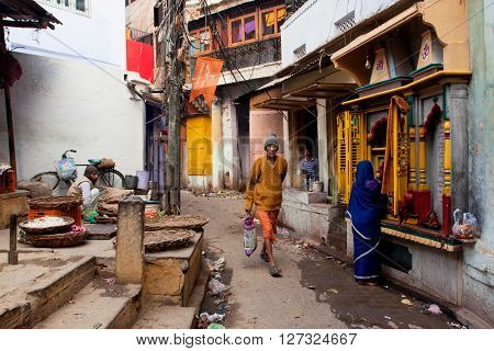 VARANASI, INDIA - JANUARY 2, 2013: Traditional street life with a sellers a praying woman and passers-by people at morning on January 2, 2013. Varanasi urban agglomeration had a population of 1435113
