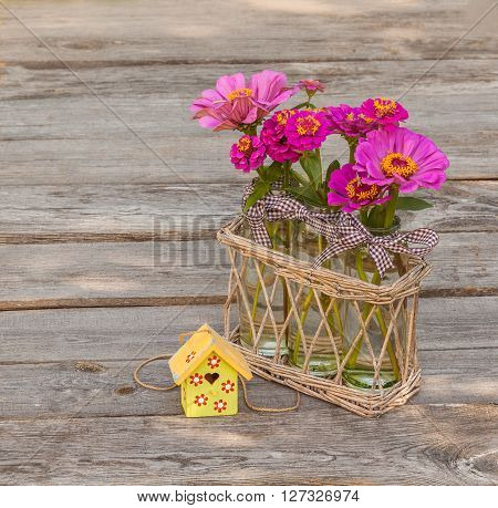 Bouquet zinnias next to a decorative starling house on a wooden table