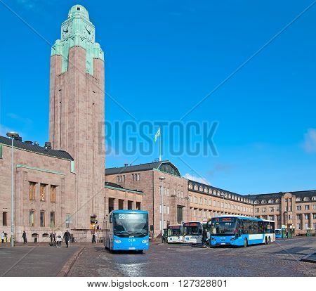 HELSINKI, FINLAND - APRIL 23, 2016: Local buses on The Helsinki Railway Square (Rautatientori) near The Central Railway Station Building. The station building was designed by Eliel Saarinen.