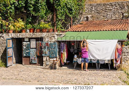 POCITELJ BOSNIA AND HERZEGOVINA - SEPTEMBER 1 2009: Local resident using his garage as a shop to sell local handicraft and embroidery to tourists