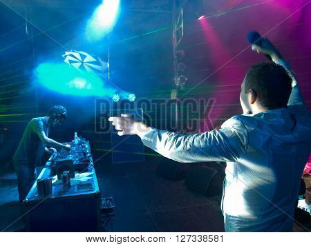 The presenter and the DJ on the stage against the laser rays ** Note: Visible grain at 100%, best at smaller sizes