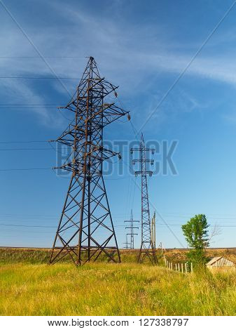 Electric power transmission lines in the field next to small house