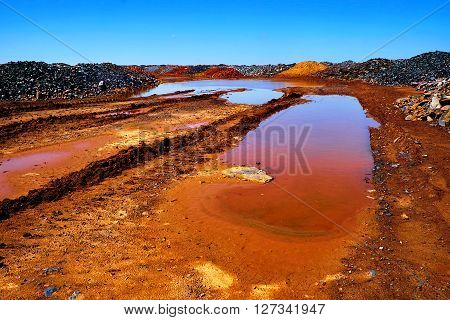 Red road with puddle in open-cast mine and dumps of depleted iron ore on background