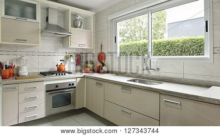 the kitchen of photography with appliances and cabinets in beige.