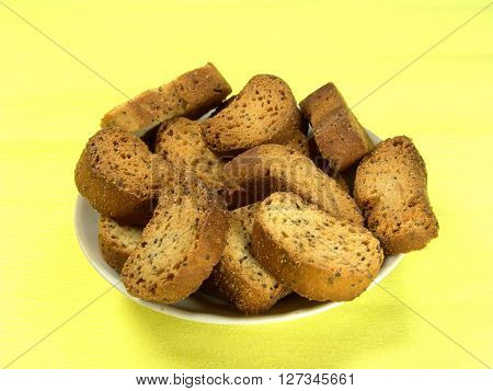 rusks on a plate close-up on a yellow background
