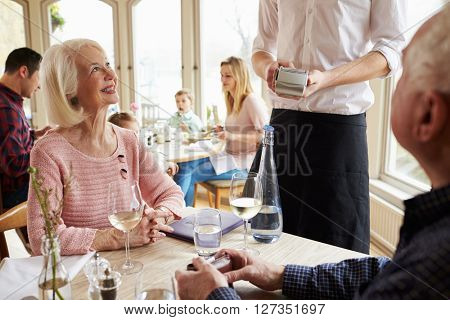 Senior Couple With Waiter Paying Bill In Restaurant