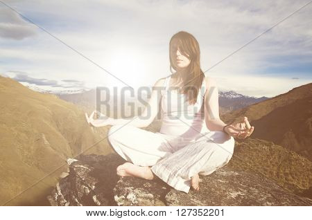 Young woman meditating in the wilderness with beautiful mountain range as a background.