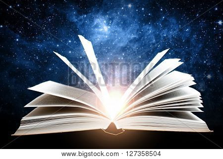 Opened magic book with sun and galaxy. Elements of this image furnished by NASA.