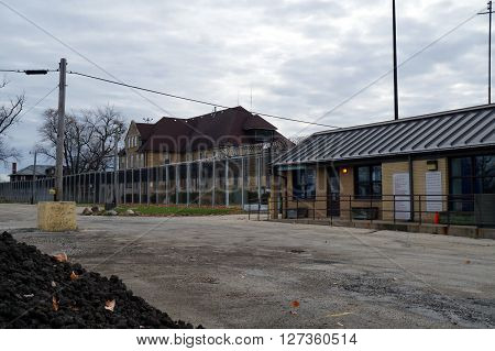 JOLIET, ILLINOIS / UNITED STATES - JANUARY 1, 2013: The entrance to the Joliet Juvenile Prison, and the Administration Building behind a razor wire fence.
