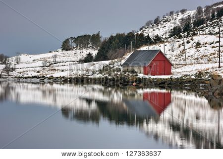 Rorbuer reflected along Vagspollen in the Lofoten Islands Norway in the winter. poster