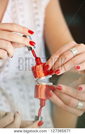 Woman applying red nail polish on her fingers - focus on the brush.