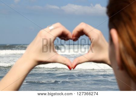 Female hand making a heart shape, ocean's waves in the background