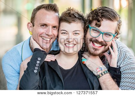 Three gender fluid friends pose and smile poster