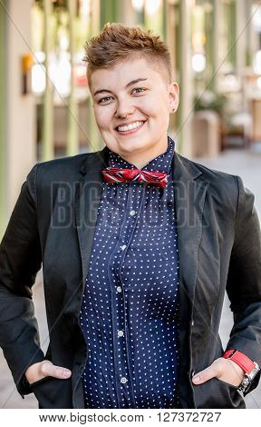 Smiling dapper young gender fluid woman on city sidewalk poster
