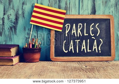 a chalkboard with the question parles catala? do you speak Catalan? written in Catalan, a pot with pencils, some books and the flag of Catalonia, on a wooden desk