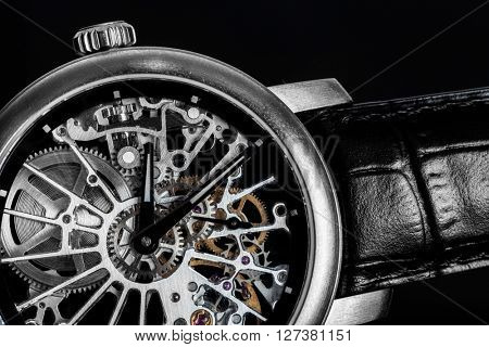Elegant watch with visible mechanism, clockwork close-up. Luxury, men's vintage accessory. Time, fashion concept.