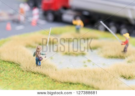 Miniature anglers at a pond near road close up