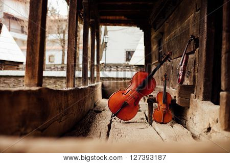 Cello And Violin Leaning On A Porch