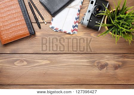Ð¡amera and supplies on office wooden desk table. Top view with copy space