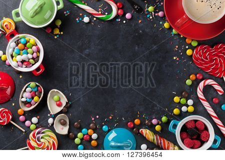 Colorful candies and coffee cup frame on stone background. Top view with copy space