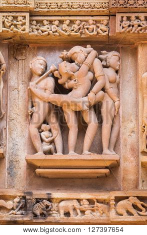 Cultural heritage of India - the sculptures made of sandstone being couple in one of Kama-Sutra poses on a wall of the temple of Kandariya-Mahadeva Khajuraho the Province of Madhya Pradesh.
