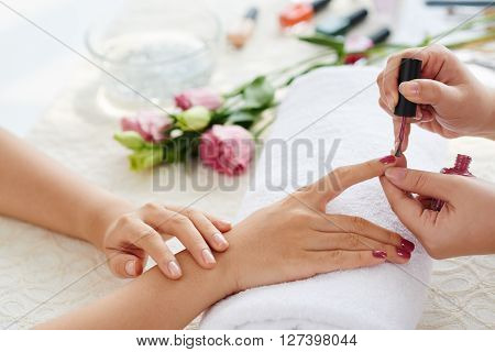 Manicurist polishing fingernails with beautiful marsala color